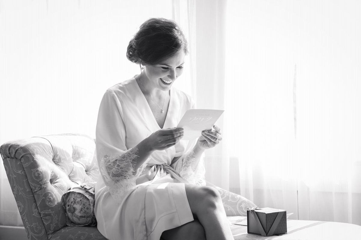 Chic Butlers Courtyard Wedding Candid Bride reading letter